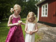 Two girls holding marguerite flowers in front of house — Stock Photo
