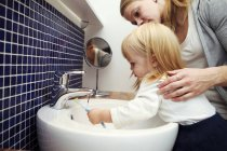 Mother helping daughter in brushing teeth — Stock Photo