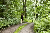 Woman in sportswear jogging on rural road — Stock Photo