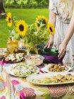 Woman preparing bowls on picnic table — Stock Photo
