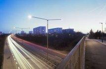 Langzeitbelichtungsaufnahme von Autobahn und Wohngebäuden, die nachts beleuchtet sind — Stockfoto