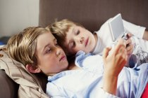 Brothers playing on game console, selective focus — Stock Photo