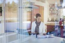 Femme mature lisant des documents et utilisant un ordinateur portable — Photo de stock