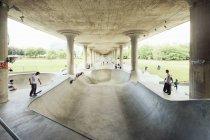 Молодые люди катаются под мостом — стоковое фото