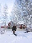 Людина очищення двір з снігу штовхач — стокове фото