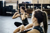 Two young women training with barbells in gym — Stock Photo