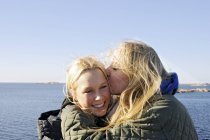 Молодая женщина целует друга в щеку, избирательный фокус — стоковое фото