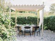 Vista frontal de la mesa bajo el gazebo en el jardín - foto de stock