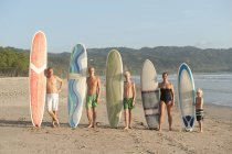 Family with surfboards on beach, focus on foreground — Stock Photo