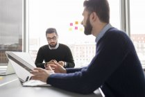 Two men talking and using laptop in office — Stock Photo
