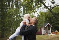Pai segurando filha contra árvores, foco em primeiro plano — Fotografia de Stock
