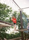 Girl walking on rope in adventure park — Stock Photo