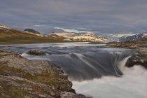 Vista panorámica de la cascada que fluye y gama de la montaña - foto de stock