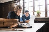 Jóvenes profesionales independientes mirando la pantalla del ordenador portátil - foto de stock