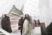Friends standing in front of Triangeln railway station, seen through window — Stock Photo