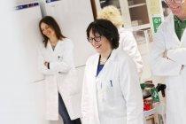 Ученые в лабораторных халатах стоят улыбаясь в лаборатории — стоковое фото
