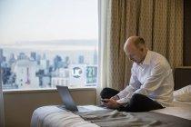 Empresario con smartphone en habitación de hotel con el paisaje urbano de Tokio en ventana - foto de stock