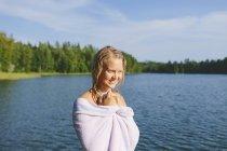 Donna avvolta in un asciugamano al lago, concentrarsi sul primo piano — Foto stock
