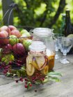 Preserved apples in jars and fresh apples in metal basket — Stock Photo