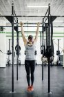 Young woman training on horizontal bar in gym — Stock Photo