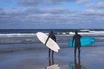 Hombres que van a surfear a Bondi Beach al amanecer - foto de stock