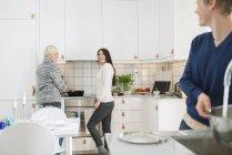 Две женщины и мужчина на домашней кухне, фокус на фоне — стоковое фото