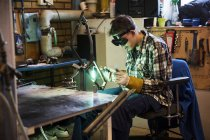 Young man in protective eyewear welding metal — Stock Photo