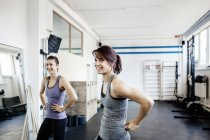 Two young women standing in gym and smiling — Stockfoto