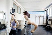 Zwei junge Frauen im Fitness-Studio stehen und Lächeln — Stockfoto