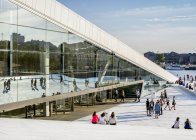 Осло оперного театру з людьми, сидячи на сходах і ходити на набережній на заході сонця — стокове фото