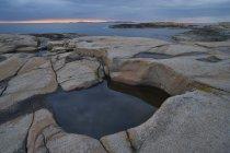 La côte rocheuse et ciel coucher de soleil nuageux — Photo de stock