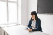 Young woman using mobile phone at desk — Stock Photo