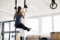 Back view of young woman training on gymnastic rings — Stock Photo
