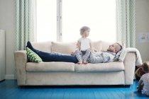Vater spielt mit Töchtern im Wohnzimmer — Stockfoto