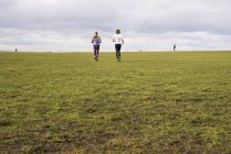 Young man and woman jogging in green meadow — Stock Photo