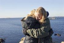 Junge Frauen am Strand, selektiven Fokus umarmt — Stockfoto