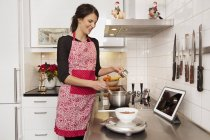 Side view of woman cooking in kitchen — Stock Photo