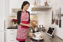Vista lateral de la mujer cocinando en la cocina - foto de stock