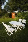 White table and chairs in sun lighted garden — Stock Photo
