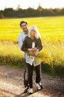 Улыбающаяся молодая пара, обнимающая поле, фокусирующаяся на переднем плане — стоковое фото