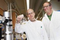 Scientifiques avec fiole de laboratoire, foyer différentiel — Photo de stock