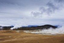 Vapore sopra sorgenti termali con catena montuosa all'orizzonte — Foto stock