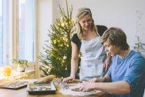 Coppie che preparano i biscotti di Natale presso la sala da pranzo — Foto stock