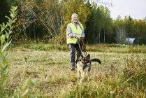 Портрет добровольца с собакой, помогающего спасателям найти пропавших людей — стоковое фото