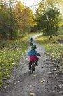 Meninos de bicicleta no parque, vista traseira — Fotografia de Stock
