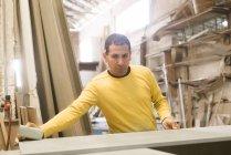 Hombre carpintero pulido de madera en el taller - foto de stock