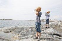 Due ragazzi che guardano attraverso il binocolo sulla riva rocciosa dell'arcipelago di Stoccolma — Foto stock
