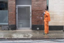 Mid adult man cleaning building facade with pressure washer — Stock Photo
