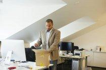 Uomo d'affari aprendo il pacchetto in ufficio e guardando verso il basso — Foto stock