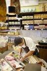 Jeune homme travaillant en magasin, se concentrer sur le premier plan — Photo de stock